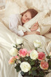 Beautiful sleeping woman in bed with roses