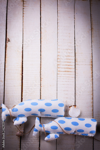 Toys whales and seashells on wooden background