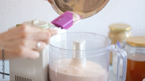 Closeup video of a woman pouring whisked eggs into blender