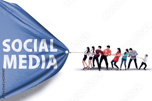 Businessteam pulling a banner of social media