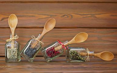Cuatro botellas con pimientas de color y cucharas de madera