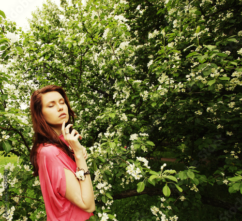 young lovely woman in spring flowers