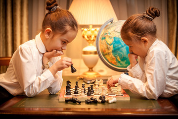 Two sisters in school uniform playing chess