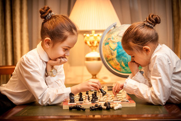 Two girls in school uniform playing chess at cabinet