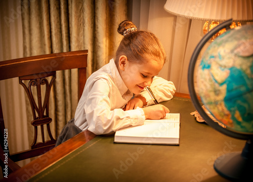 Closeup portrait of little girl doing geography homework