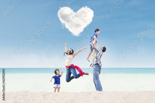 Happy family under heart cloud at beach