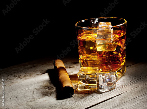 Glass of aged whiskey with cigar and ice cubes
