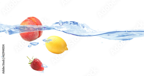 Juicy fruits dropped into water