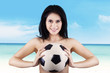 Woman smiling while holding soccer ball