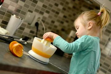 Petite fille faisant fraîche et saine jus d'orange