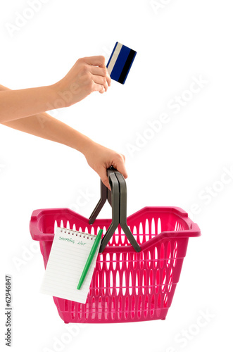 Woman holding a market basket,a shopping list and a crdit card.
