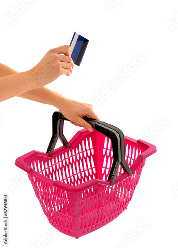 Woman hand holding a shopping basket and a credit card.