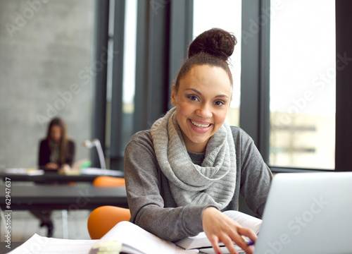 Happy young woman studies in the library