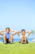 People exercising - Couple doing sit ups outdoors