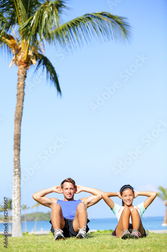 People training sit ups outside - fitness couple