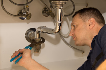 Plumber repairs kitchen sink