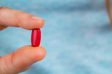 Close-up of fingers holding a red pill.