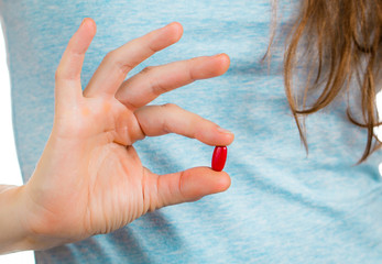 Fingers holding a red pill.