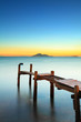 Seascape with sunset and wooden bridge