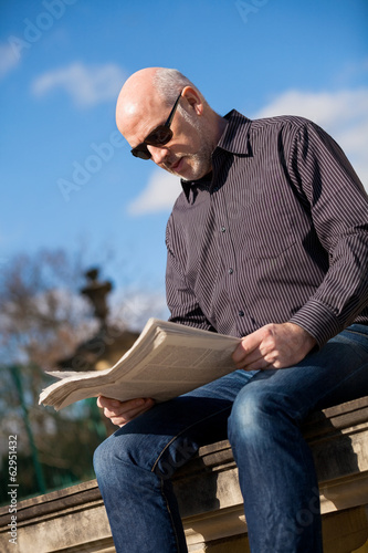 Man sitting reading a newspaper on a stone wall