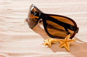 sunglasses in dry sand and starfish