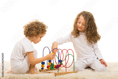Sisters playing with wooden toy