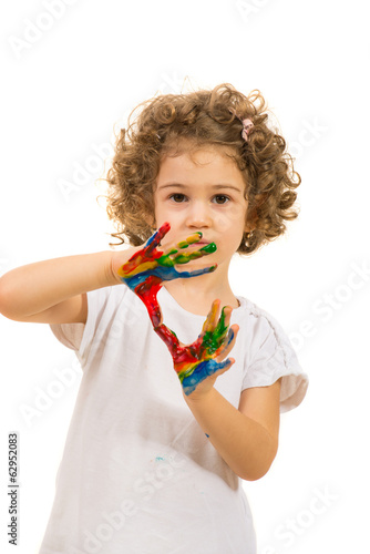 Little girl with colorful hands in paints