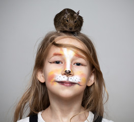 girl painted as a cat with grey mouse on the head