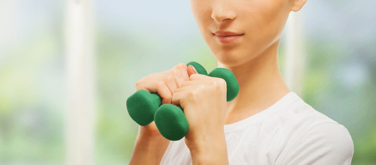 Smiling woman with green dumbbell