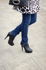 Girl's leg with black boots on a high heel.