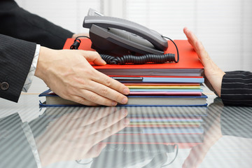 businessman is receiving files,folders  and telephone from cowor