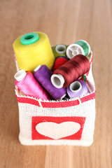 Colorful bobbins of thread  in bag, on wooden background
