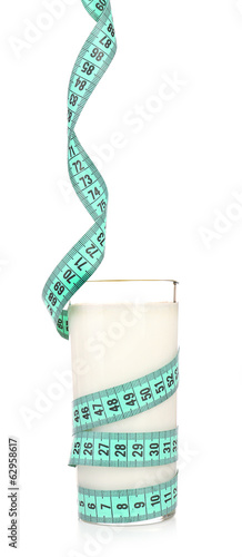Glass of milk with measuring tape isolated on white