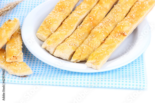 Tasty bread sticks on plate on color napkin, isolated on white
