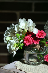 Beautiful still life with small pink roses and freesia flowers