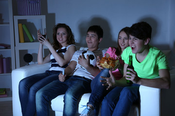 Group of young friends watching television at home of