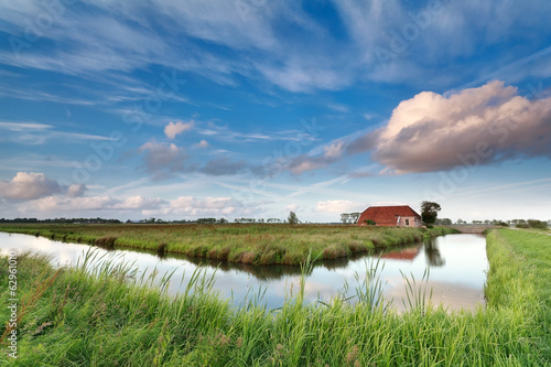charming farmhouse by river over blue sky