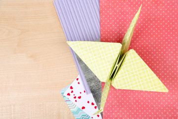 Origami crane and color papers on wooden table