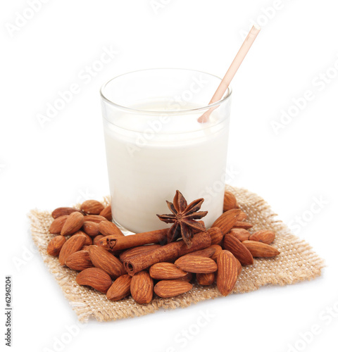 Almond milk in glass with almonds, isolated on white