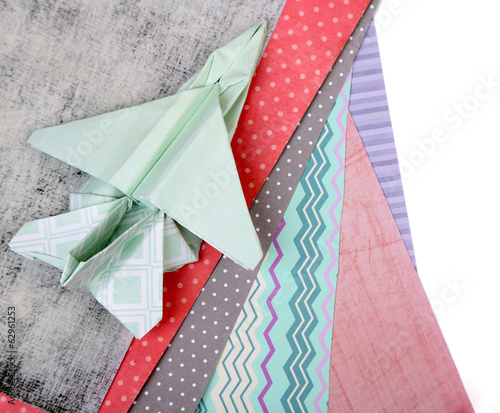Origami airplane and color papers isolated on white