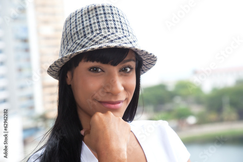 Brazilian woman with hat looking at camera