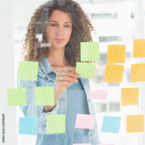 Focused designer looking at sticky notes on window