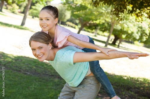 Happy mother carrying daughter at park