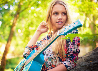 Vintage looking photo of a beautiful girl with a guitar