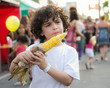 Hispanic child boy eating corn on the cob in a street festival