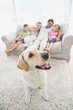 Happy family sitting on couch with their pet yellow labrador