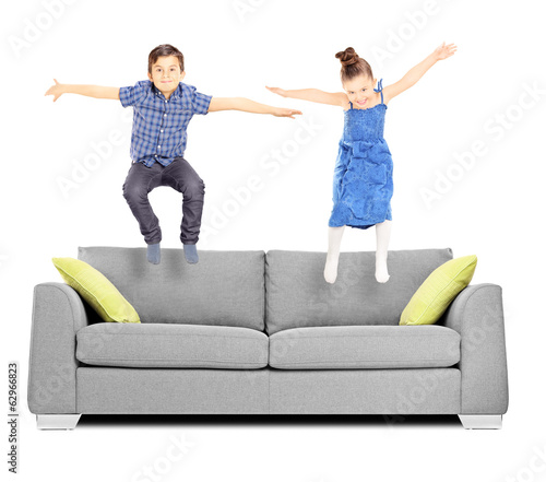 Brother and sister jumping on sofa