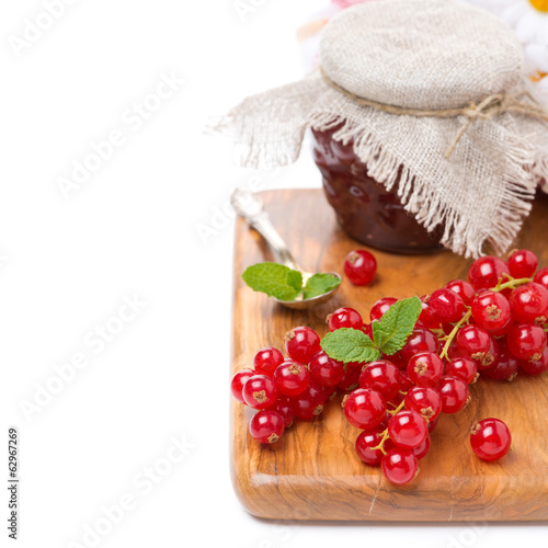 fresh red currant and berry jam on a wooden board, isolated