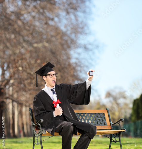 Excited college graduate taking a selfie in park
