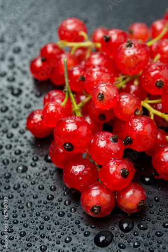 red currant with drops of water on black background, close-up